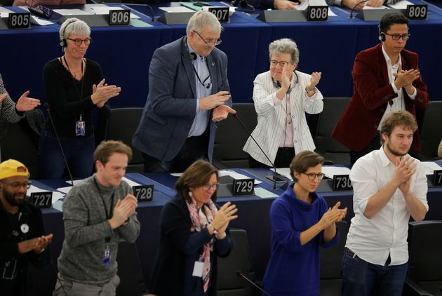 Members of the European Parliament react after a vote during a voting session in Strasbourg, France,...