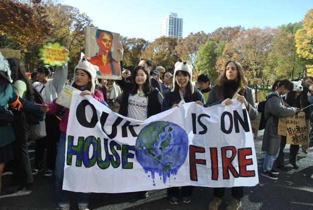 気候マーチでメッセージの書かれた横断幕を掲げる若者たち
