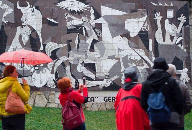 スペイン北部ゲルニカで、ピカソの「ゲルニカ」の壁画を眺める人々(2017年)