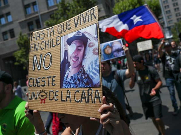 A woman holds a sign that reads in Spanish: