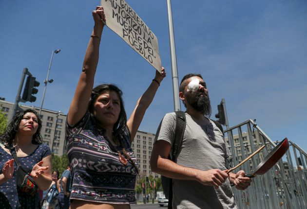 Marcelo Herrera, his eye bandaged from an injury he received during recent protests, bangs on a pan as a woman holds a sign with a message that reads in Spanish: