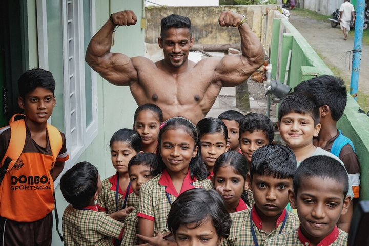 Chitharesh poses for a photo withchildren from a local school who came to meet 'the man who has put Kerala on the map'.