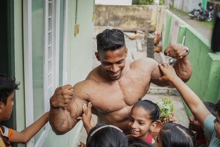 Chitharesh answers the children's questions and lets them feel his biceps.
