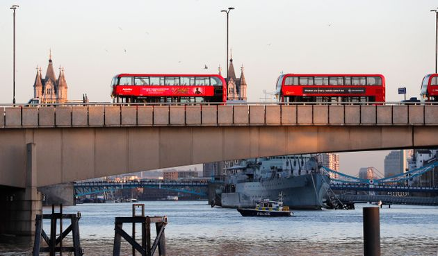 A police boat on the River Thames as abandoned buses are parked on London