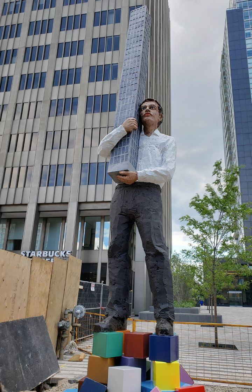 A 25-foot statue of a man holding a condo building outside of a Toronto condo development.