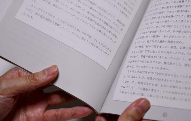 HIV感染について自ら書いた手記を読む女性=東京