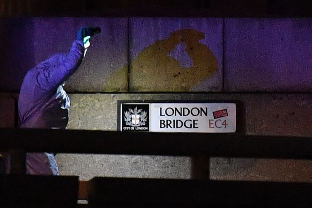 A police forensic officer lights the scene on London Bridge where armed police officers shot a suspect...