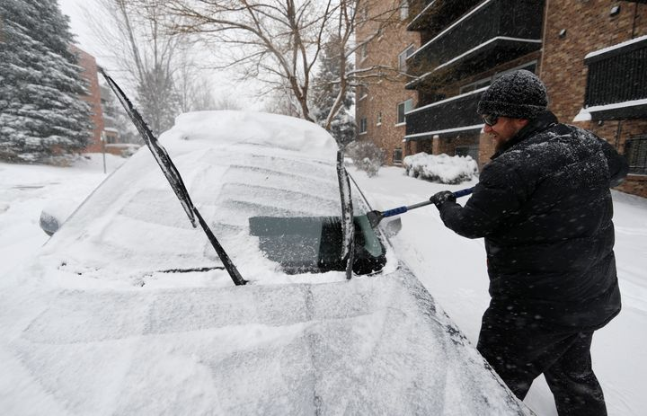 Szymon Lobocki, a rocket engineer from Denver, clears off his Subaru to drive to work in a south suburb as a storm packing sn