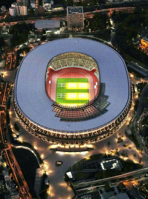完成を迎え照明がともった新国立競技場。黄色の部分は芝生の養生のために当てられたライト=2019年11月29日夜、朝日新聞社ヘリから、嶋田達也撮影