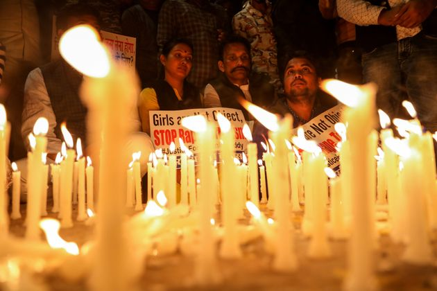 People attend a candle light march to protest against the alleged rape and murder of a 27-year-old woman...