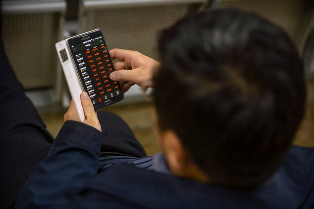 A Chinese investor uses a smartphone as he monitors stock prices at a brokerage house in Beijing, Monday,...
