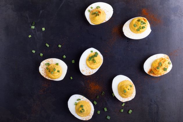Deviled eggs topped with green onion and paprika over gray background viewed from