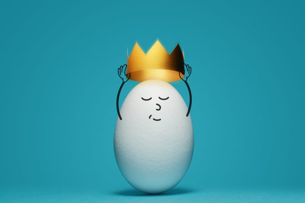 A white egg is dressing a gold crown on blue background. Concept of