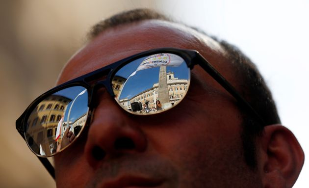 Montecitorio Palace is reflected in sunglasses of a 5-Star Movement supporter during a protest in Rome, Italy, October 12, 2017. REUTERS/Alessandro Bianchi