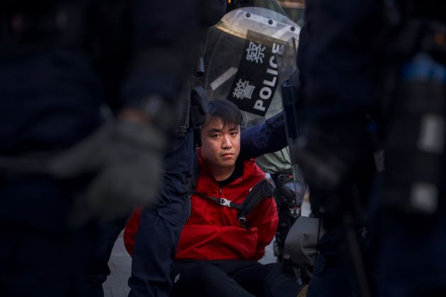 A pro-democracy protester is detained by policemen during a rally in Hong Kong, Sunday, Dec. 1, 2019....