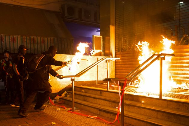 Pro-democracy protesters set fire at an entrance gate of Whampoa MTR station in Hong Kong, Sunday, Dec....