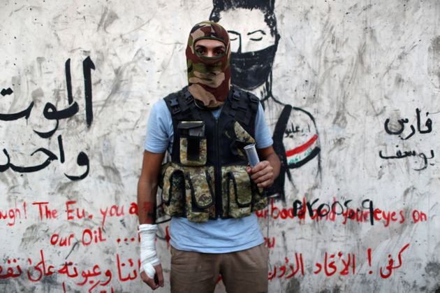 Hussein Karim Hashem, an Iraqi demonstrator, poses for a photograph during the ongoing anti-government...