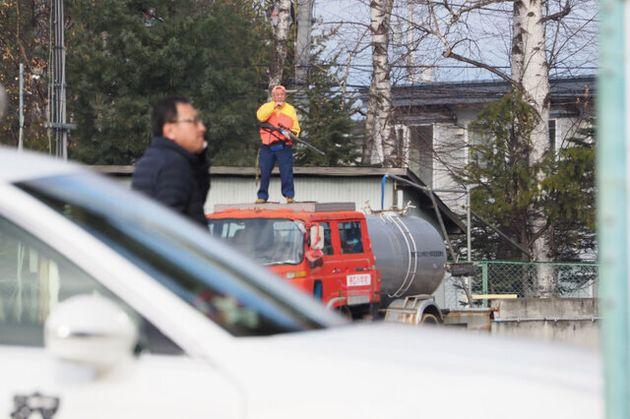 クマが逃げ込んだ北海道帯広市の小学校で、校庭にクマが飛び出して来た場合に備えるハンター=2019年12月1日、午前9時57分、北海道帯広市