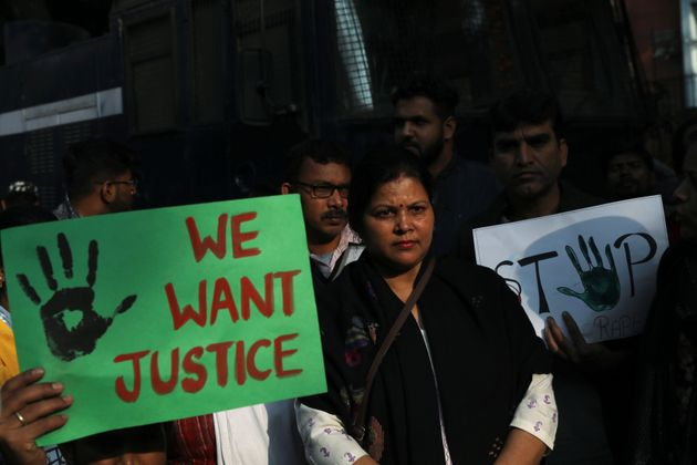 People hold placards and shout slogans as they take part in a protest against the alleged rape and murder...