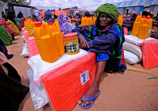Un desplazado somalí aguarda mientras se le entrega comida y agua en Mogadiscio, en