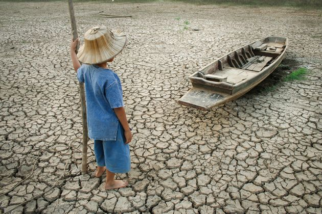 Children standing near the wooden boat on cracked earth. Metaphor for Global warming and Climate