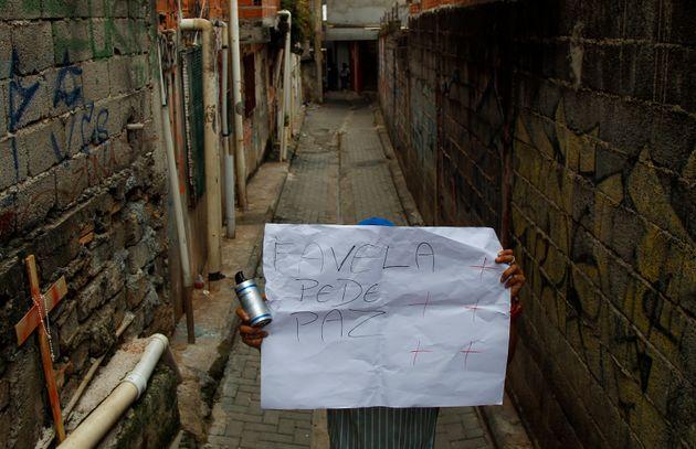 Homem segura cartaz sobre paz nas favelas em Paraisópolis, após a morte de nove pessoas...