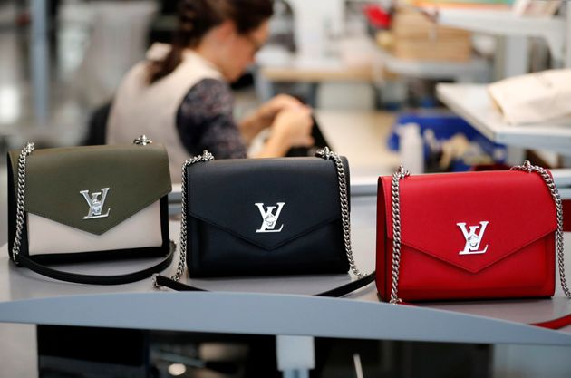 Louis Vuitton handbags are displayed as an employee works in a Vuitton new high-end garment factory in...