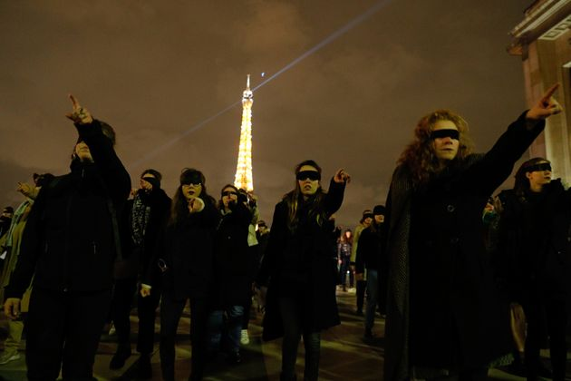 Women wearing black blindfolds take part in a flash mob at the Trocadero esplanade in Paris on November...