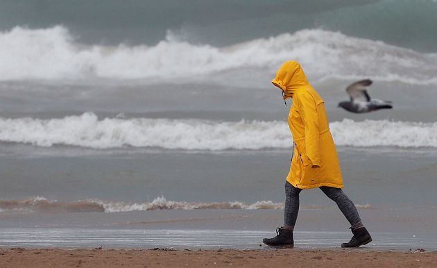 Una persona pasea por la playa de la Malvarrosa bien protegida contra la