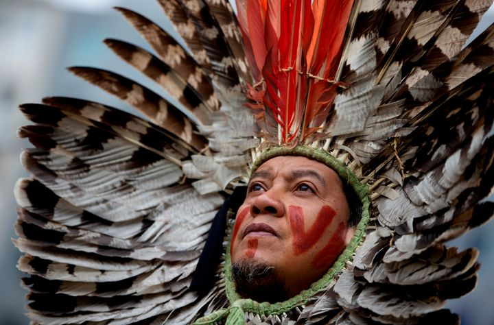A Brazilian Indigenous leader protests against forest destruction in front of the European Union headquarters in Brussels on
