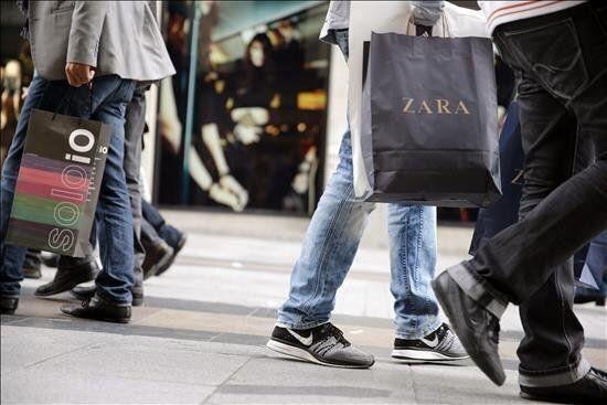 Varias personas pasean con bolsas de compras por la céntrica calle Preciados de