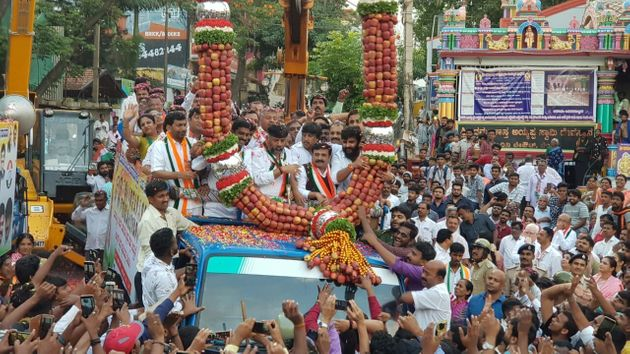 An apple garland being lowered around Congress leader D.K. Shivakumar. Apple garlands have now become...