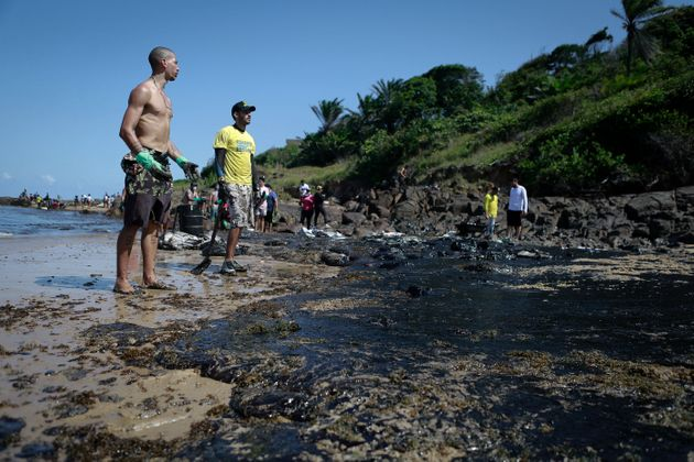 Voluntários removem óleo na praia de Santo Agostinho, Pernambuco, em 21 de outubro de