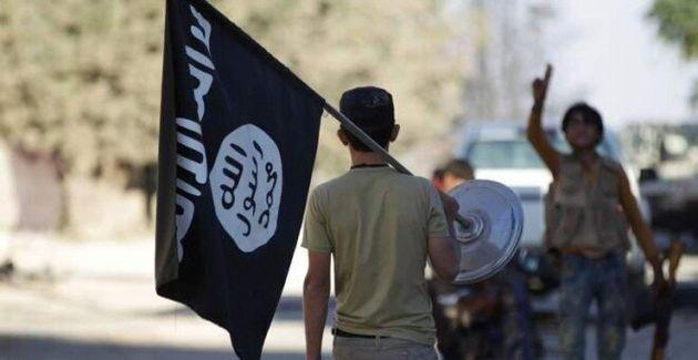 Un chico exhibe la bandera del Estado Islámico por la calle, en una foto de