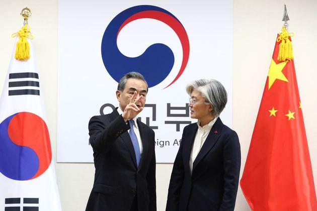 South Korea's Foreign Minister Kang Kyung-wha (R) stands with China's Foreign Minister Wang Yi (L) during...