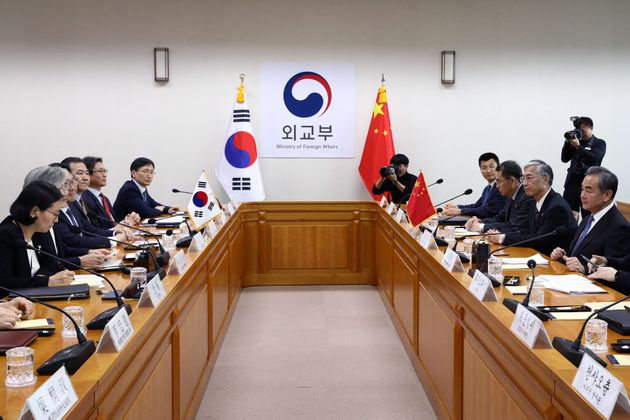 South Korea's Foreign Minister Kang Kyung-wha talks with Chinese Foreign Minister Wang Yi during their...