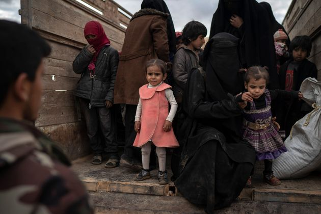 Women and children exit the back of a truck to be screened by U.S.-backed Syrian Democratic Forces (SDF)...