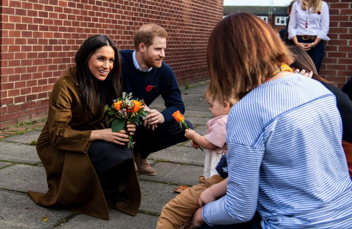 Bonnie and Maggie Emanuel give a posy of flowers to Meghan during a visit at Broom Farm Community Centre in Windsor on