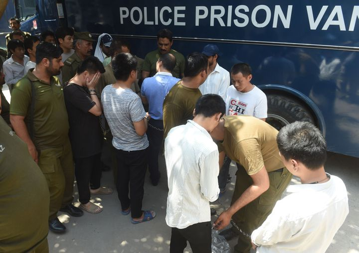 Pakistani policemen escort handcuffed Chinese nationals as they arrive in court in Lahore on June 10, 2019. The men are accus