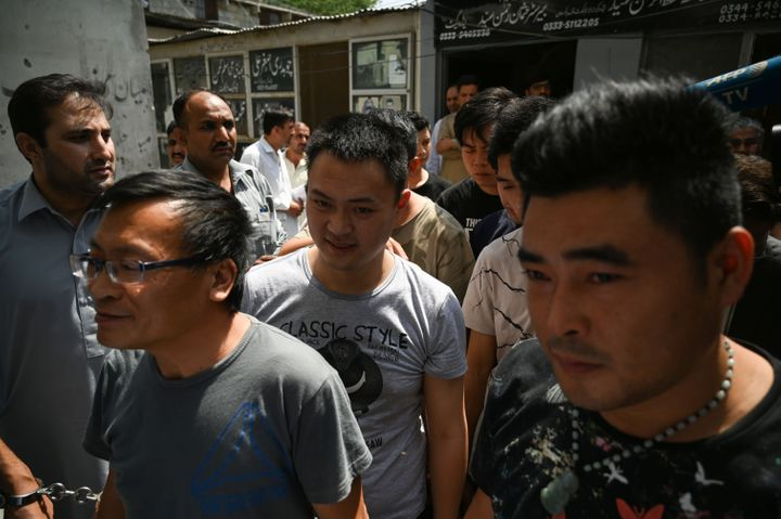 Detained Chinese nationals walk together as they arrive at a court in Islamabad after being arrested by the Pakistani Federal
