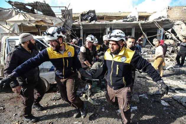 Les Casques blancs de la Défense civile syrienne tirent une victime des débris dans un...