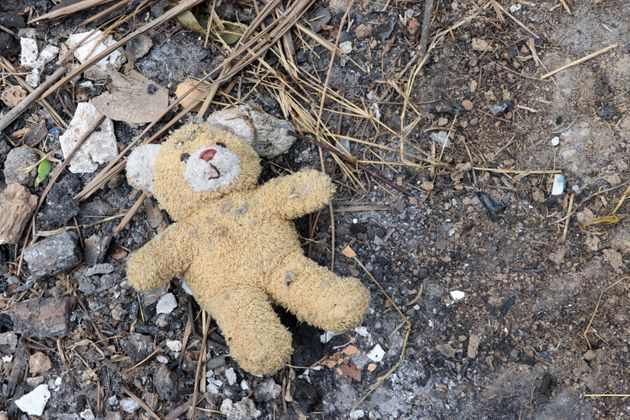 Old dirty teddy bear neglected on the ground soil. End of