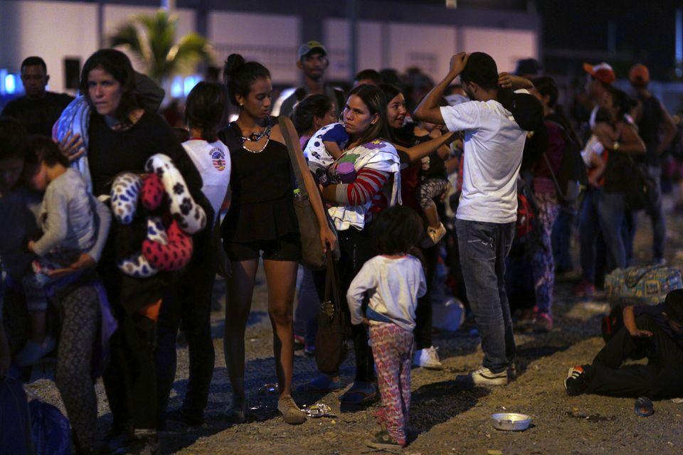 Un grupo de venezolanos hace cola para pasar un control de inmigración en la frontera entre Ecuador...