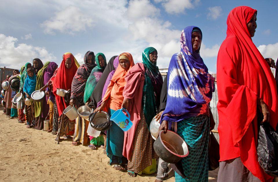 Un grupo de mujeres espera a recibir comida distribuida por voluntarios locales en un campo de desplazados...