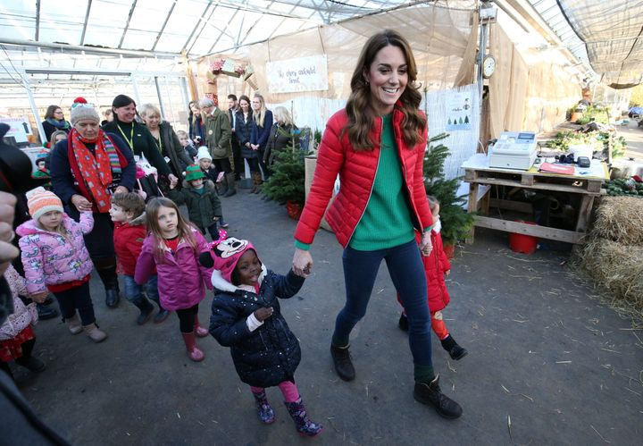 The Duchess of Cambridge leads children to pick a Christmas tree during a visit to Peterley Manor Farm in Buckinghamshire, Br