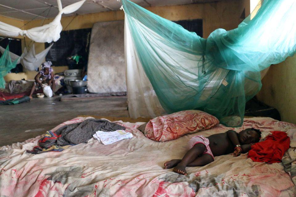 Un niño duerme en una habitación compartida con otros desplazados por inundaciones en Lokoja,...