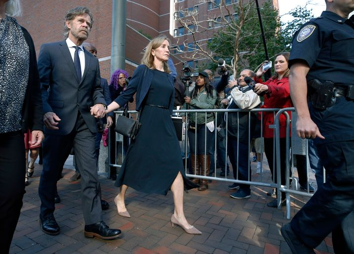 Felicity Huffman leaves federal court with her husband, William H. Macy, wearing a navy dress and jacket on Sept. 13, 2019, in Boston.