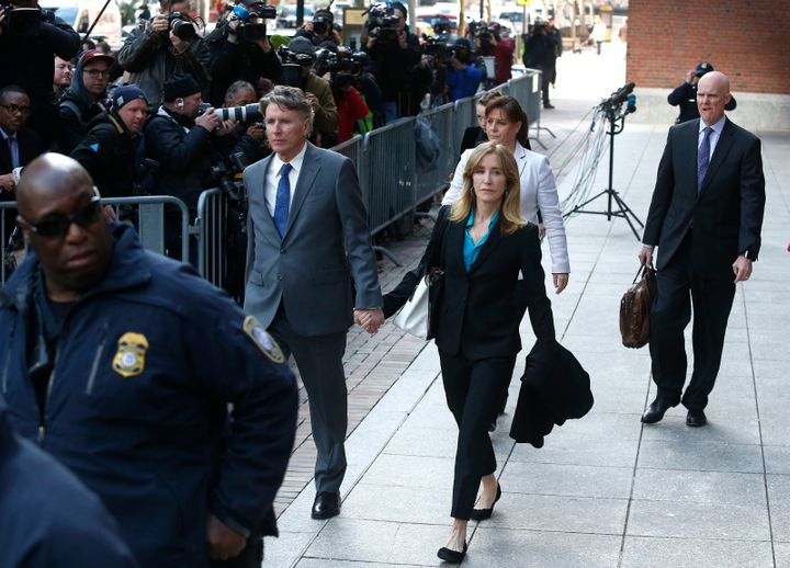 Felicity Huffman, in blue shirt at center, leaves the John Joseph Moakley United States Courthouse in Boston on April 3, 2019.