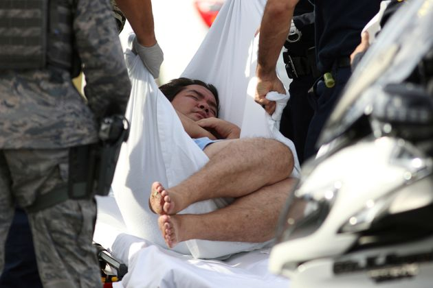 An unidentified male is taken away by officers outside the main gate at Joint Base Pearl Harbor-Hickam,...
