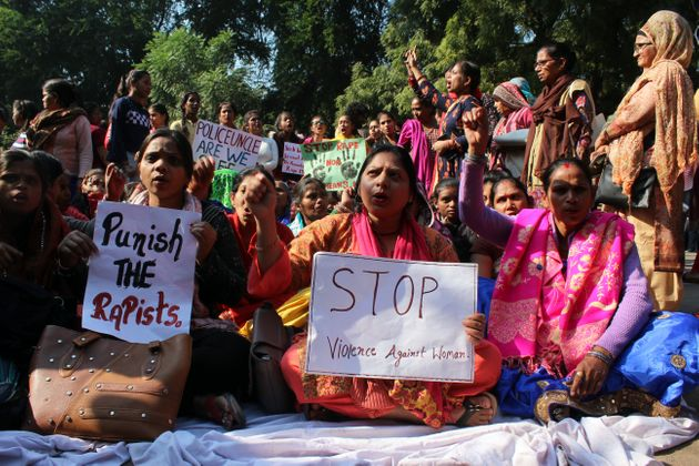 Protestors holds a placard and shout slogans during a sit-in protest as Delhi Commission for Women (DCW)...